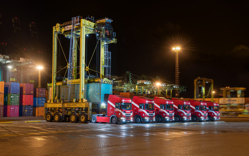 Sevral trucks from Transport Th. Wouters picking up containers at night at container terminal.